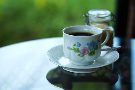 relaxing with hot black americano coffee Serve in white cup in garden in the afternoon