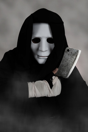 nightmarish: Ghost Killer man in mask and hood hold chopping knife, costume for Halloween night
