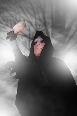 underhand: Ghost Killer man in mask and hood hold chopping knife, costume for Halloween night