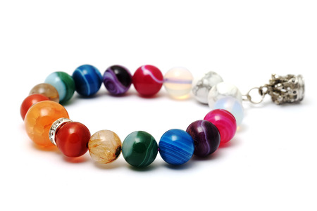 Colorful of agate,jasper bracelet decorate with silver crown pendant with white isolated background