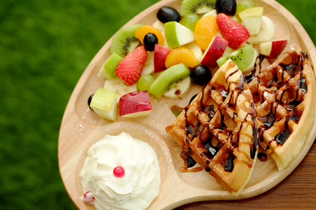 Waffle pour chocolate sauce and fruit mixed Served whipping cream and drink with Hot cappuchino for appetizer Stock Photo