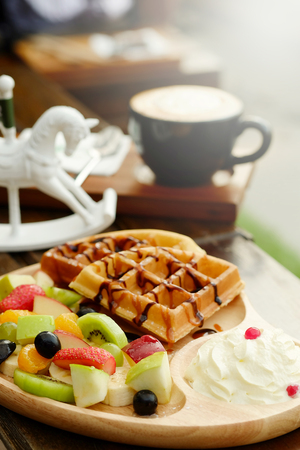 Waffle pour chocolate sauce and fruit mixed Served whipping cream and drink with Hot cappuccino for appetizer Stock Photo