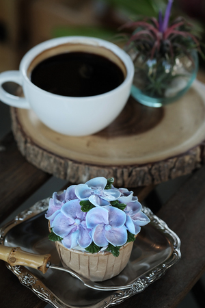 Blue cupcake design cream like blue Hydrangea flower Served with hot black coffee on wooden table background and have some space for write wording