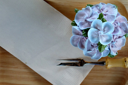 Blue cupcake design cream like blue Hydrangea flower Served on wooden tray with brown paper napkin and little fork,have some space for write wording