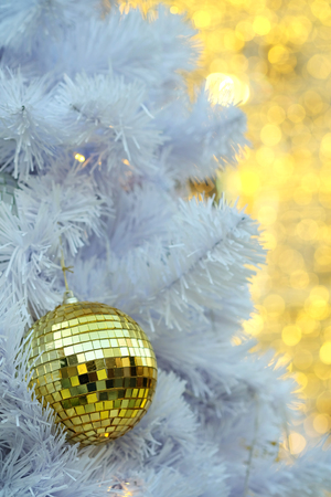 Golden Christmas ball items on white pie and yellow bokeh form LED lighting background. In merry Christmas and happy New Year festival  Golden Christmas ball items on white pie and yellow bokeh form LED lighting background. In merry Christmas and happy Ne