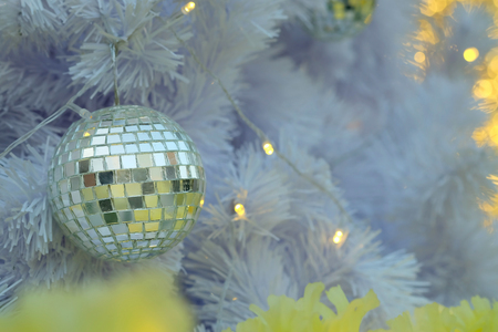 Golden Christmas ball items on white pie and yellow bokeh form LED lighting background. In merry Christmas and happy New Year festival