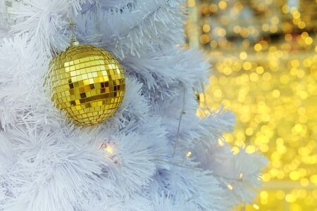 led lighting: Golden Christmas ball items on white pie and yellow bokeh form LED lighting background. In merry Christmas and happy New Year festival