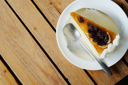 A piece of cake with raisin topping on rough wooden table.Have some space for write wording Stock Photo