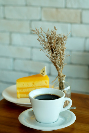 Hot black coffee and Orange cake on wooden table and white brick wall