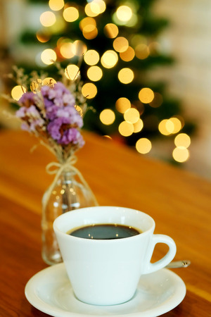 hot black coffee on wooden table with bokeh background