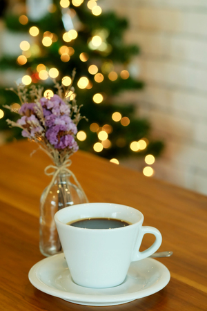 relent: hot black coffee on wooden table with bokeh background