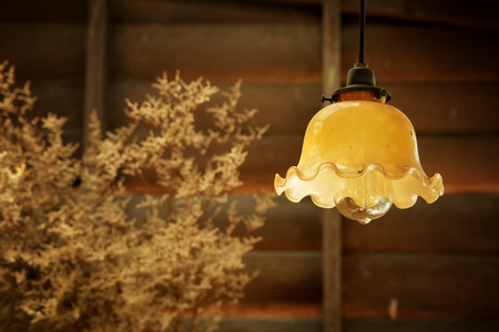 dowdy: retro hanging lamp in vintage style with rough wooden wall decorate by Dry grass   background Stock Photo