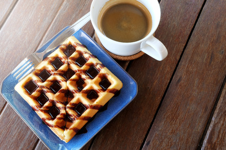 niños en recreo: Hot coffee and Waffles with chocolate sauce on wooden table background.Have some space for write wording