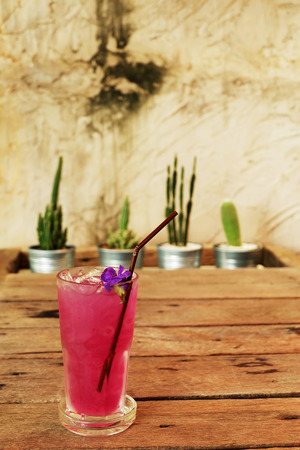 cool butterfly pea juice on wooden table decorate by cactus in aluminum pots and rough Cement wall background