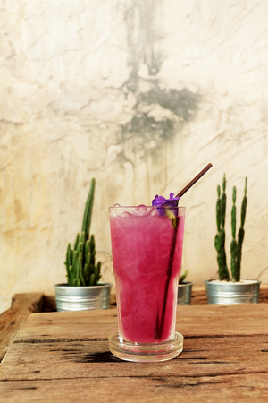 soppy: cool butterfly pea juice on wooden table decorate by cactus in aluminum pots and rough Cement wall background