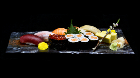 Asian cuisine or Japanese food. Sushi medium set on wooden plate with black isolated background