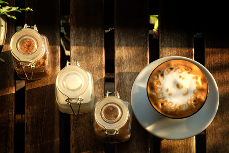 suger: The sun foam design in hot latte coffee and suger on rough wooden table