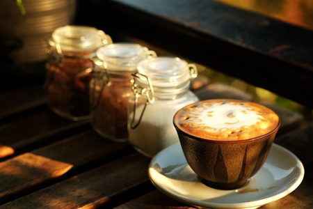 The sun foam design in hot latte coffee and suger on rough wooden table