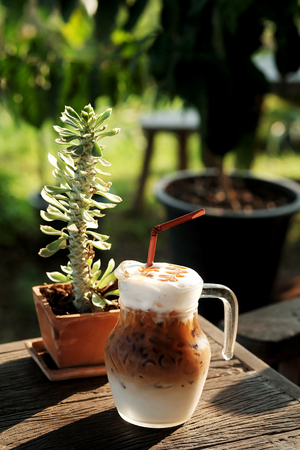 cool ice caramel macchiato coffee on rough wooden table in topical garden. have some space for write wording