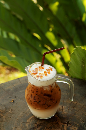 potation: cool ice caramel macchiato coffee on rough wooden table in topical garden. have some space for write wording