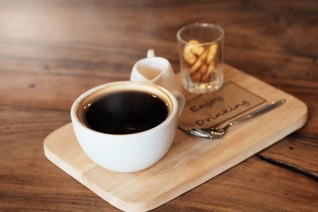 avid: hot black coffee in white cup Served with mini biscuit on rough wooden plate Stock Photo