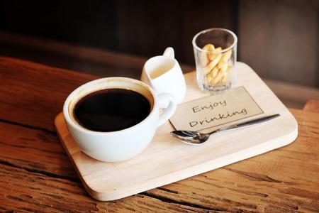 Caffè nero caldo in tazza bianca Servito con mini biscotto su piastra di legno grezzo Archivio Fotografico - 77739225