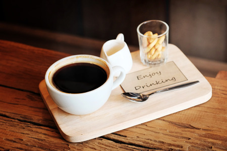 hot black coffee in white cup Served with mini biscuit on rough wooden plate Stock Photo