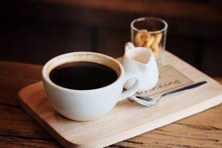 大まかな木製プレートにミニ ビスケットでホワイト カップ役立ったで熱いブラック コーヒー