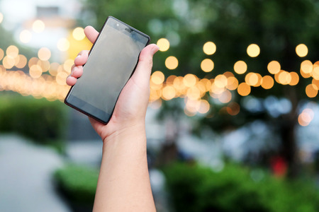 smart phone in hand with bokeh in park in evening time background. And have some space for write wording