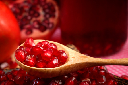 Pomegranate Set. Good healthy by Pomegranate seed on wooden spoon and cool Pomegranate juice set on red Themes tone background. have some space for write wording