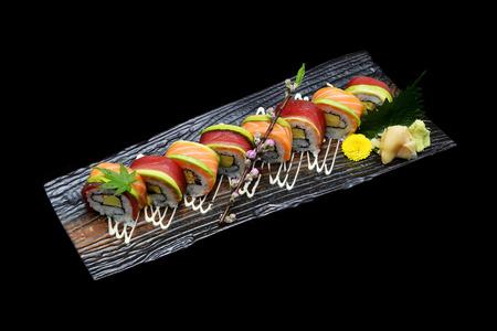masticate: Tuna sushi maki roll and Salmon sushi maki roll. Japanese sushi fish roll on black isolated background. Japanese tradition fusion food style.