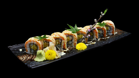 masticate: grill Salmon sushi maki roll with Spicy cream sauce. Japanese sushi fish roll on black isolated background. Japanese tradition fusion food style.