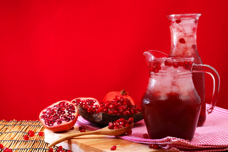rubicund: Pomegranate Set. Good healthy by Pomegranate seed on wooden spoon and cool Pomegranate juice set on red Themes tone background. have some space for write wording