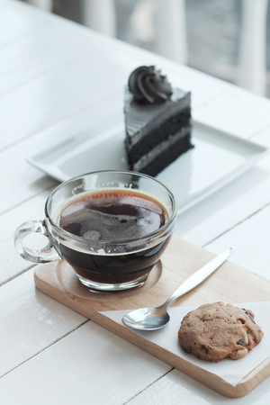 hot americano black coffee and A piece of charcoal cake on white wooden table. Have some space foe write wording Stock Photo