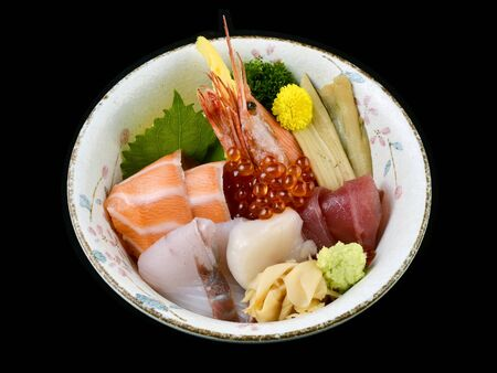 Chirashi sashimi don or mixed fresh sea food on rice in ceramic of Japanese tradition cuisine food with black isolated background Stock Photo