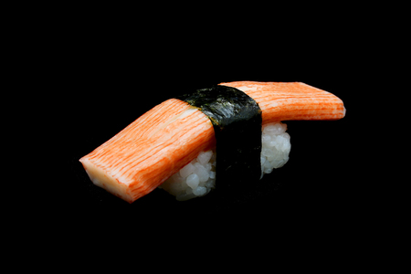 Kani sushi or Crab stick top on rice rap by Seaweed. Japanese tradition food withe black isolated background