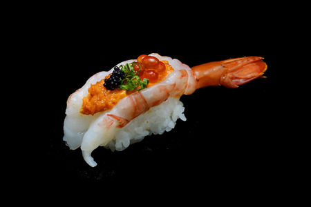 Botan ebi sushi or Spacial premium king shrimp sushi mixed by ikura and caviar top on Japanese rice. Japanese tradition food with black isolated background Stock Photo