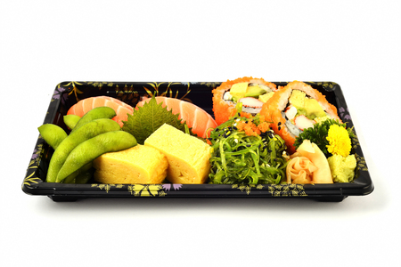 Salmon sushi and California maki and tamoko tamago fill with pigeon pea and spicy seaweed salad Japanese tradition food in delivery low cost box set Stock Photo