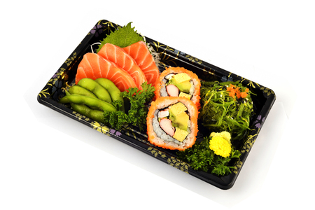 Salmon Sashimi and California Maki  fill with Pigeon pea and spicy Seaweed salad Japanese tradition food in delivery low cost box set