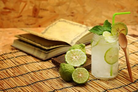 Kaffir lime So, Bergamot soda Cool drink, Thailand tradition Herb for Treatment of Acid Reflux, with Oriental Earth tone map background.Have some space for write wording