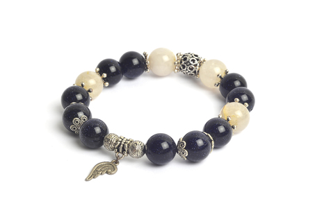 supplement a richness and good fortune by blue sand stone (Silver sand stone) and golden rutillated quartz  bracelet amulet with white isolated background