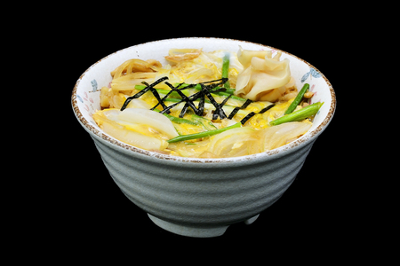 Japanese tradition food. katsu donis  a fried pork with egg and onion in a rice in bowl with black isolated background Stock Photo