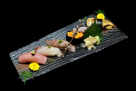 일본 전통 음식. 검은 격리 된 배경 가진 나무 접시에 설정하는 독점 프리미엄 스시