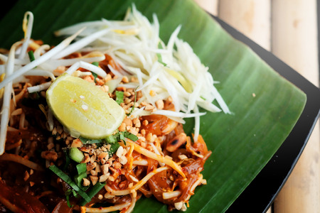 Phat thaior Pad thai is a famous Thailand tradition cuisine with fried noodle served on banana leaf.and have some space for wording background