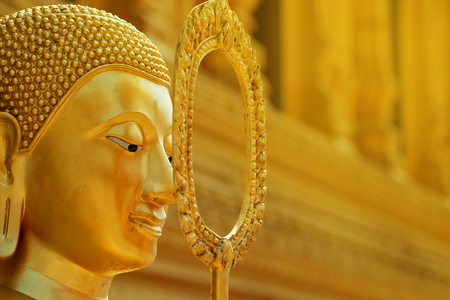 golden calm face of Buddha statue with golden background. Have some space for text or wording about Principles Stock Photo