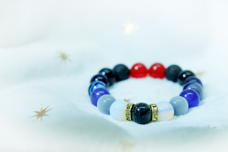 Colorful in white blue black red lucky stone bracelet bead on white towel background.fashion with believe in Add charm,property, healthy in wonderful life.