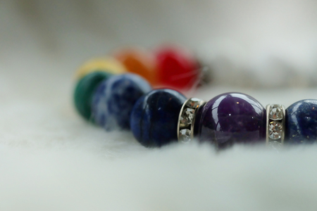 mineral Chakra color luck fortune stone bracelet on white wool background.  Amulet accessories for good good lucky fortune and happy life