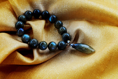 Labradorite lucky stone on golden fabric background. Amulet accessories for good lucky fortune and happy life Archivio Fotografico