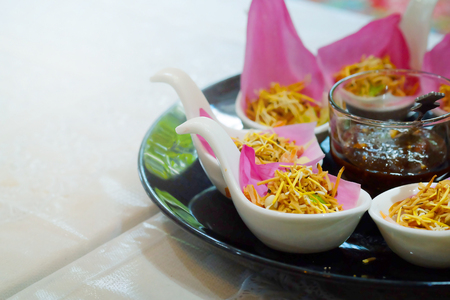 Meung Kum kleeb Bua Thailand royal traditional appetizer make by Roasted coconut mix with many Thai herb wrapping with pink lotus petal Served with Sweet dip mix with Groundnut. Stock Photo