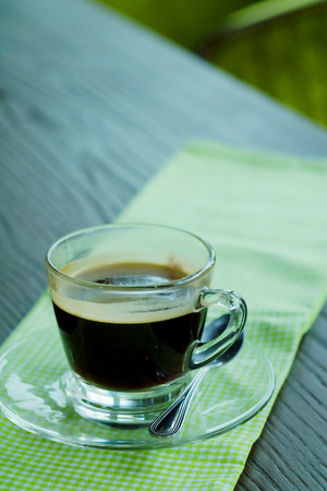 Hot Americano black coffee in transparent cup one wood wooden table with green tone.Have some space for write wording